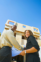 Portrait of smiling young couple with construction plans outside new home under construction.