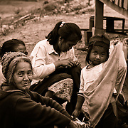A little girl from a hilltribe in Lao shies away from the camera, as her grandmother looks over her.