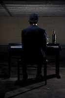 A man dressed in black plays a piano in a dimly lit parking garage.  A bottle of wine and glasses on the piano.