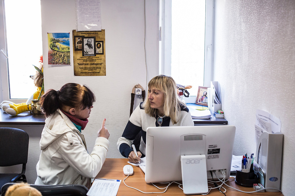 DNIPROPETROVSK, UKRAINE - OCTOBER 10: Olga Nalyvaiko (L), who fled from the Eastern Ukrainian city of Luhansk due to fighting, speaks to a worker at The Aid of Dnipro, a charity organization providing assistance to displaced people, on October 10, 2014 in Dnipropetrovsk, Ukraine. The United Nations has registered more than 360,000 people who have been forced to leave their homes due to fighting in the East, though the true number is believed to be much higher. (Photo by Brendan Hoffman/Getty Images) *** Local Caption *** Olga Nalyvaiko