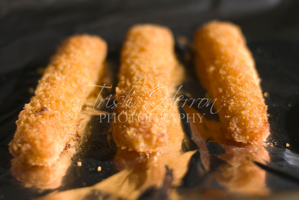 Freshly cooked fish sticks on aluminum foil await a child's lunchtime.