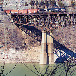 A southbound Norfolk Southern freight train rides high over the Cumberland River, crossing the tall bridge in Burnside, KY.