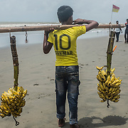 A young boy selling bananas on the beach of Cox's Bazar, Bangladesh