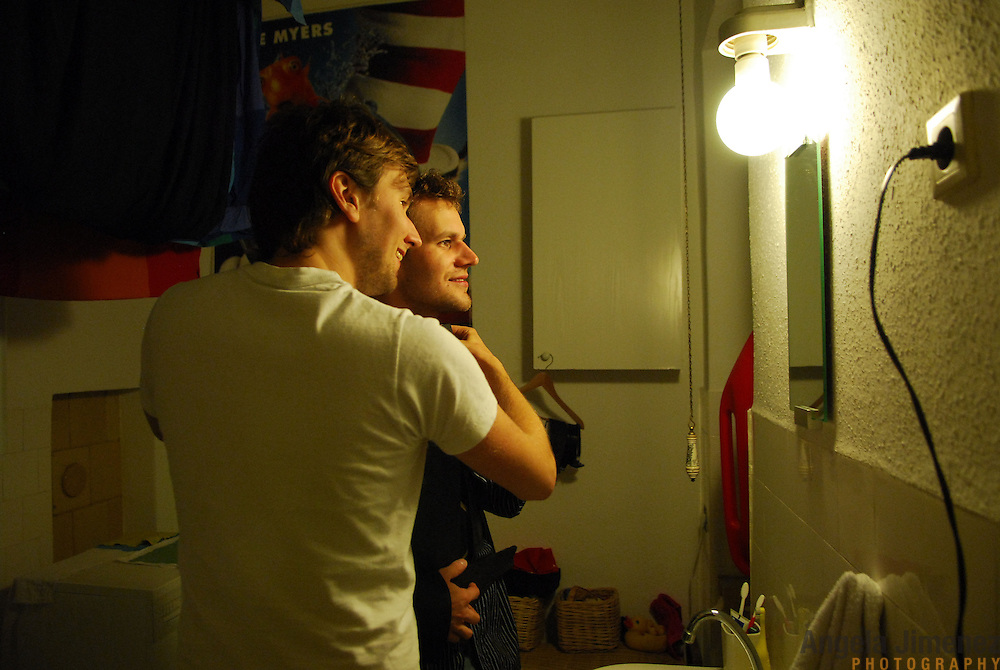 """World Champion same-sex ballroom dancer Robert Tristan Szelei, right, tries on one of his competition shirts with dance partner Gergely Darabos, left, at Darabos' apartment in Budapest, Hungary on October 18, 2006, where the pair are hosting and will compete in the 2nd annual World Championship Same-Sex Ballroom Dancing competition in their hometown on October 21, 2006. ..Szelei and Darabos , who are known as the """"Black Swans,"""" are the reigning world champions in men?s Latin same-sex ballroom dancing. The 2nd annual World Championship and the Csardas Cup, the first-ever Eastern European same-sex ballroom competition will be held at the Korcsarnok arena, the pinnacle event of the blossoming same-sex ballroom scene...Szelei and Darabos went on to win the men?s Standard division and finished fourth in the Latin division. ..The event was organized by the US-based World Federation of Same-Sex Dancing, which hosted the first World Championship Same-Sex championships in 2005 in Sacramento, California. The Black Swans did a large amount of the coordination and planning in Budapest, a city that had never seen an event of this kind. When government funding fell through, they secured funding from patron Desire (accent on the ?e?) Dubounet, owner of the local Club Bohemian Alibi drag club. ..The World Championship events are newly recognized, but same-sex dancers have been competing on a national and international circuit for a number of years, especially in Europe, including at the Eurogames, the Gay Games, the London Pink Jukebox Trophy and the Berlin Open, among others. Countries including the United States, the Netherlands, Germany and, now, Hungary, hold their own national same-sex championships. Hungary held its first national championships in April 2006...Szelei and Darabos spent three months at the Sacramento Dancesport same-sex dance school in California this summer, on the first scholarship offered by the World Federation. The men both got their early training as oppo"""