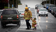 Two and a half year-old Imogen arrives hand in hand with her dad John Boyd at a Fireman's protest over contract negotiations at the opening of a new Fire Station in Mt Roskill, Auckland, New Zealand. September 2009. <br />