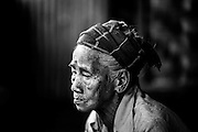 MYITKYINA, MYANMAR - MARCH 13th, 2016: In Hkum Lu, 90, the eldest resident in Shwezet IDP camp. Nearly 500 people were forced to relocate here in 2011 because of escalated fighting between the Kachin Independence Army, KIA, and the Burmese government, which has been in various states of conflict since 1994. She says she often cries at night thinking of and missing her previous home.