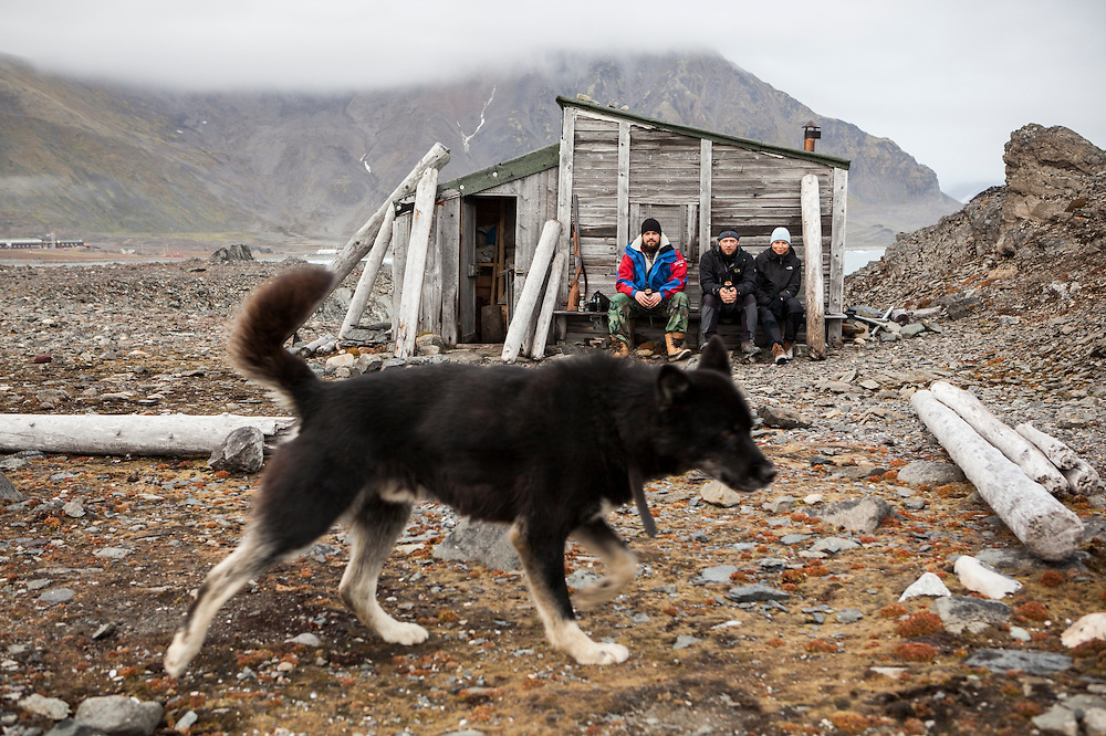 Station cook Dominik Petelski (l-r) and glaciologists Dariusz Ignatiuk and Agnieszka Piechota sit together against a historic hut still standing outside the Polish Polar Station in Hornsund, Svalbard. One of the station's huskies stands guard.