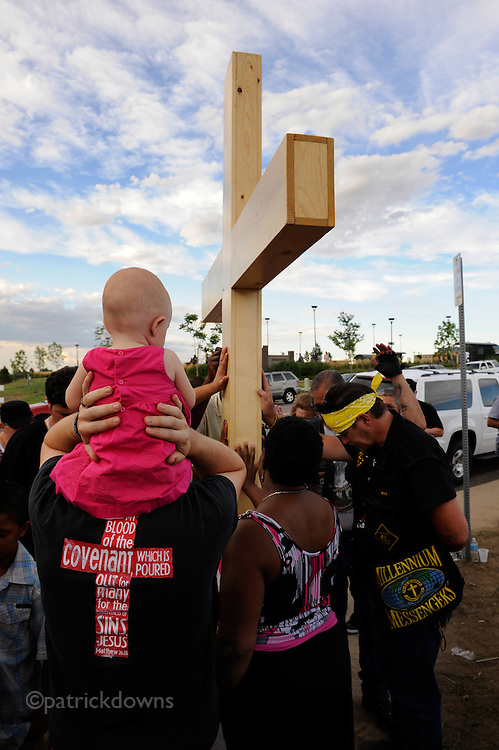 Aurora, CO: 9 month old baby girl Lily McKeel, in pink, rides on her father Ryan's shoulders near a cross erected at an impromptu shrine. The group prayed for the 12 killed in the mass theatre shooting rampage.
