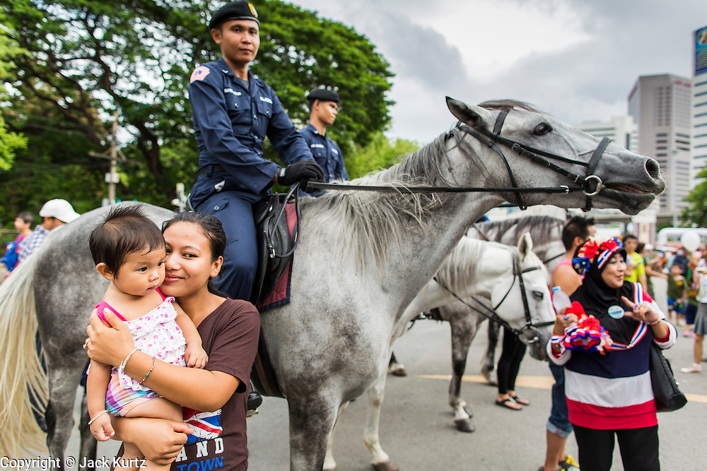 """15 JUNE 2014 - BANGKOK, THAILAND: Thais pose for pictures with members of the Royal Thai Police mounted police unit during a """"Return Happiness to Thais"""" party in Lumpini Park in Bangkok. The Thai military junta, formally called the National Council for Peace and Order (NCPO), is sponsoring a series of events throughout Thailand to restore """"Happiness to Thais."""" The events feature live music, dancing girls, military and police choirs, health screenings and free food.   PHOTO BY JACK KURTZ"""