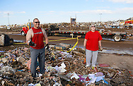 Terry Wallace (L) cracks a joke about using a candlestick as a dumbell with his mother-in-law Sandra Booth-Knight at her tornado-destroyed home across the street from the Plaza Towers elementary school (background) in Moore, Oklahoma May 22, 2013. A massive tornado tore through a suburb of Oklahoma City, wiping out whole blocks and killing at least 24.   REUTERS/Rick Wilking (UNITED STATES)
