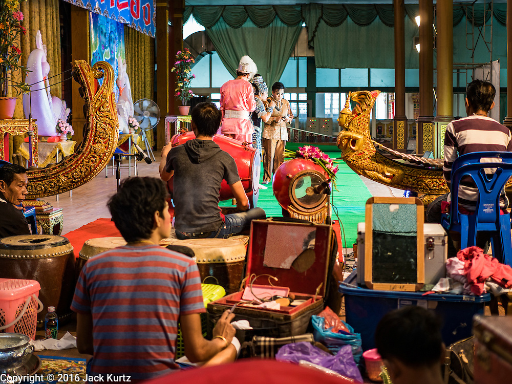 "30 JANUARY 2016 - NONTHABURI, NONTHABURI, THAILAND: Members of the cast get into makeup and costume while musicians accompany members of the cast on stage during a ""likay"" show at Wat Bua Khwan in Nonthaburi, north of Bangkok. Likay is a form of popular folk theatre that includes exposition, singing and dancing in Thailand. It uses a combination of extravagant costumes and minimally equipped stages. Intentionally vague storylines means performances rely on actors' skills of improvisation. Like better the known Chinese Opera, which it resembles, Likay is performed mostly at temple fairs and privately sponsored events, especially in rural areas. Likay operas are televised and there is a market for bootleg likay videos and live performance of likay is becoming more rare.     PHOTO BY JACK KURTZ"