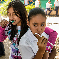 Two young teenagers brush their teeth during a demonstration Feb. 21, 2016 by the local dental brigade from Central America Medical Outreach working in La Mariposa Las Flores Lempira, Honduras. The dental brigade set up a temporary work space in a two room school just outside of Santa Rosa de Copan. CAMO  also provides, gynecological, general medicine, and breast exams during other visits throughout Honduras. Photo Ken Cedeno