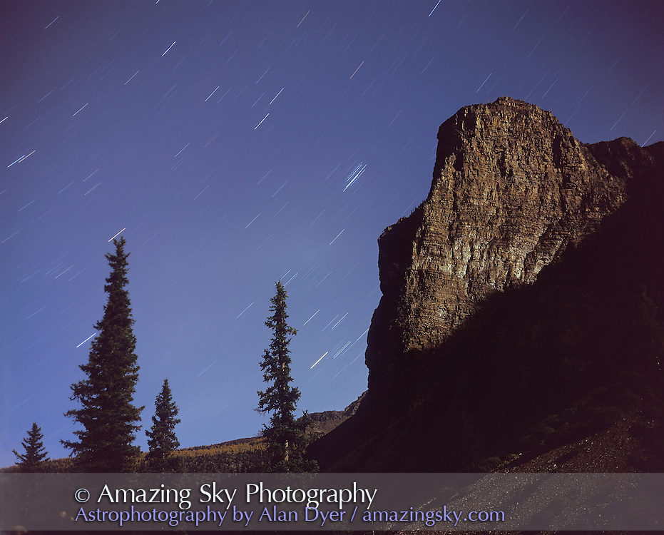 Stars of Taurus rising behind Tower of Babel peak at Moraine Lake, Banff. Taken with Plaubel Makina 6x7 camera with 80mm lens at f/5.6 and Fujichrome Velvia 50 slide film (120-format) and about 16 minute exposure in full moonlight.