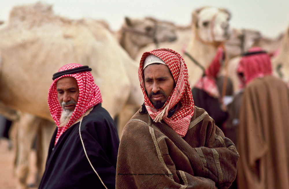 Bedouin men wearing Farrwa's (winter coat) at camel market the day after camel race at Jinadarriah, Saudi Arabia.