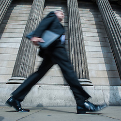 London, UK - 5 September 2014:  Businessmen walk in front of the columns of the Bank of England in the City of London