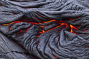 Molten pahoehoe lava flows at the end of a lava tube in Volcanoes National Park, Hawaii. Pahoehoe is the hottest – and most liquid – form of basaltic lava. This ropy pahoehoe results with the thin crust partially solidifies. Lava continues to flow behind it, pushing and folding it, not unlike an accordion.