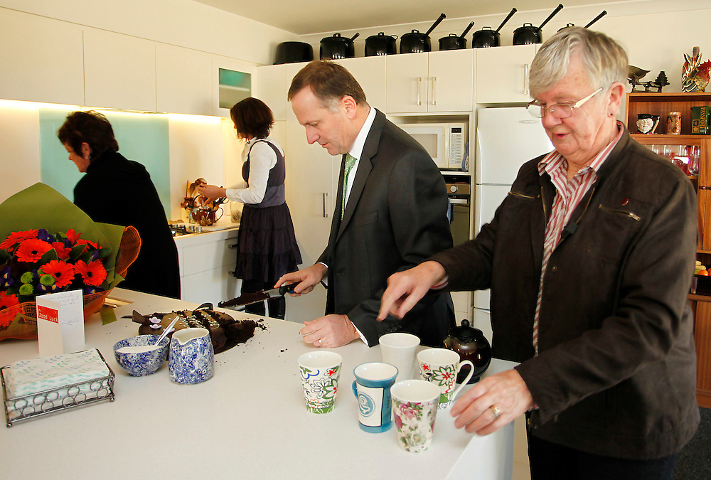 Prime Minister John Key, centre, serving cake at the new Pegasus home of Betty Simmonds, right,  after the Government purchased her red zoned land, Pegasus, New Zealand, Thursday, June 28, 2012.  Credit:SNPA / Pam Johnson