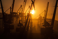 Sunrise breaks through cranes on the quay in the Black Sea port of Novorossiysk.