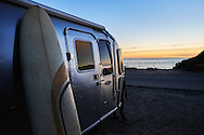 A surfboard and Airstream trailer camped out in Carlsbad State Beach, Carlsbad, California.