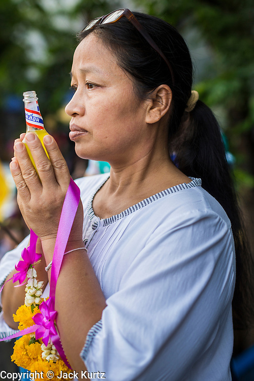 12 APRIL 2014 - BANGKOK, THAILAND: A woman prays at the Phra Buddha Sihing during the procession's stop in Thonburi. The Phra Buddha Sihing, a revered statue of the Buddha, is carried by truck through the streets of Bangkok so people can make offerings and bathe it in scented oils. Songkran is celebrated in Thailand as the traditional New Year's from 13 to 16 April. The date of the festival was originally set by astrological calculation, but it is now fixed. The traditional Thai New Year has been a national holiday since 1940, when Thailand moved the first day of the year to January 1. The first day of the holiday period is generally the most devout and many people go to temples to make merit and offer prayers for the new year.    PHOTO BY JACK KURTZ