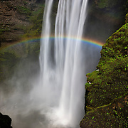 A bright rainbow stretches across Skógafoss, located in southern Iceland. Skógafoss is one of Iceland's largest waterfalls, dropping 197 feet (60 meters). According to legend, the first Viking settler in the area, Þrasi Þórólfsson, buried a treasure in a cave behind the waterfall; the waterfall is so powerful no one has been able to get it.