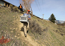 Budge Drive resident Tim Bohan gets help from a neighbor as he carries tools down from his house to his car Monday. Land owner Jody Burke has allowed his neighbors to cut through his property on a foot trail near the west end of the butte, to gain access to their homes. See this week's Jackson Hole News&Guide for more on the slow-moving slide.