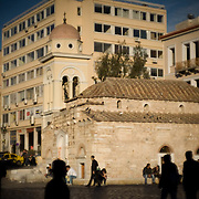 People walk past one of the oldest squares in Athens.  Monastiraki (little Monastery) square is an old part of Athens. Monasteraki square is one of the hubs that lead you into an amazing past and old artifacts that are sold in the local fea markets. Image © Angelos Giotopoulos/Falcon Photo Agency