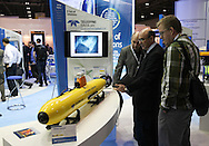 © Rob Arnold 11/03/2014. London, UK. A group of men looking at the Teledyne Gavia Offshore Surveyor Autonomous Underwater Vehicle (AUV). Oceanology International (OI), the world's largest exhibition for marine science and technology, gets underway at London's ExCeL Centre. The three day exhibition provides an opportunity for industry, academic and government organisations to share knowledge and promote improvements in technology and strategy used for operating, surveying, protecting and exploiting resources in the oceans of the world. Photo Credit : Rob Arnold