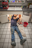"""Plumber Robert Boca fixes a leak in the kitchen sink at Clark and Mitzi's house in Calistoga, CA  707-227-0024.  """"It's been a busy day with all the rain...lots of sup-pumps failing."""""""