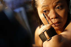 Aishah puts on her make up in her home while preparing to go out in Singapore, 07 June 2014. She uses a velcro strap to attach make up accessories to her limbs and insists on doing her make up herself.