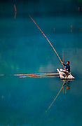 A fisherman on a bamboo raft on a reservoir in Luang Prabang, Laos.