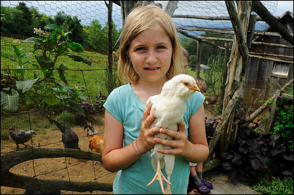 Girl with chicken at a coop