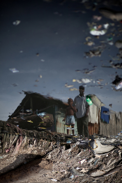 The number of cholera victims in Cité Soleil, a slum of Port-au-Prince, is increasing day by day exponentially, according to a doctor of Doctors Without Borders, essentially because of hygienic problems./// A man and his son reflect in a canal where tons of garbage are dumped, in the slum of Cite Soleil in Port-au-Prince.