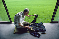 Mr. Busuke Shimoe, 84 years old, was about 1300 meters from the hypocenter of the Hiroshima atomic bomb when it detonated on August 6, 1945.  His skin was burned from much of his body, and several of the fingers on his hand were fused together.  He is examining the clothing he was wearing that morning, which is badly charred.