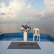 Upper-deck chair and wheel with navigator's carpet board a traditional dhoni fishing boat on the Indian Ocean, Maldives.