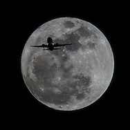 An airplane approaching Los Angeles International Airport flies past the Wolf moon (full moon) in Los Angeles, Califorina, on Wednesday January 15, 2014 (Photo by Ringo Chiu/PHOTOFORMULA.com)