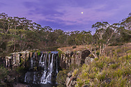 The waxing gibbous Moon over Upper Ebor Falls, on the Waterfall Way, between Armidale and Dorrigo, on the New England Tablelands, in Guy Fawkes River National Park in NSW, Australia. This was in the austral autumn (April), so after a dry summer there isn&rsquo;t a lot of water flowing over the falls. The Moon is rising into an evening twilight sky. <br /> <br /> This is a high dynamic range stack of 7 exposures to preserve the range in brightness between the bright sky and Moon, and the dark ground in the dim twilight.