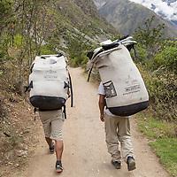 Peru, Piscacucho, Porters carrying hikers' supplies walking along Inca Trail to Machu Picchu along Urubamba River