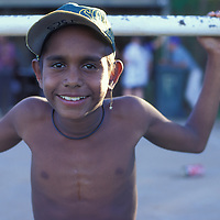 Australia, Western Australia, Aboriginal boy watches an Aussie Rules Football game from pickup truck in Kununurra