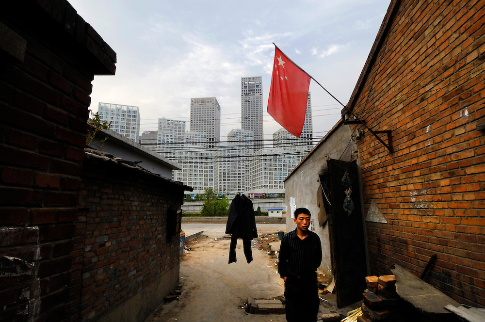 CHINA, Beijing.  View from poor hutong-style housing with communal toilets to Central Business District skyscrapers in Chaoyang.