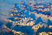 Long glaciers between mountains fade into a layer of low clouds in this aerial view of the eastern Greenland coast near Tasiilaq.