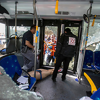 An Israeli forensic police officer inspects the body of Palestinian terrorist at the scene of a shooting attack in Jerusalem, Tuesday, Oct. 13, 2015. A pair of Palestinian men boarded a bus in Jerusalem and began shooting and stabbing passengers, while another terrorist rammed a car into a bus station before stabbing bystanders, in near-simultaneous attacks. <br /> Photo by Olivier Fitoussi.