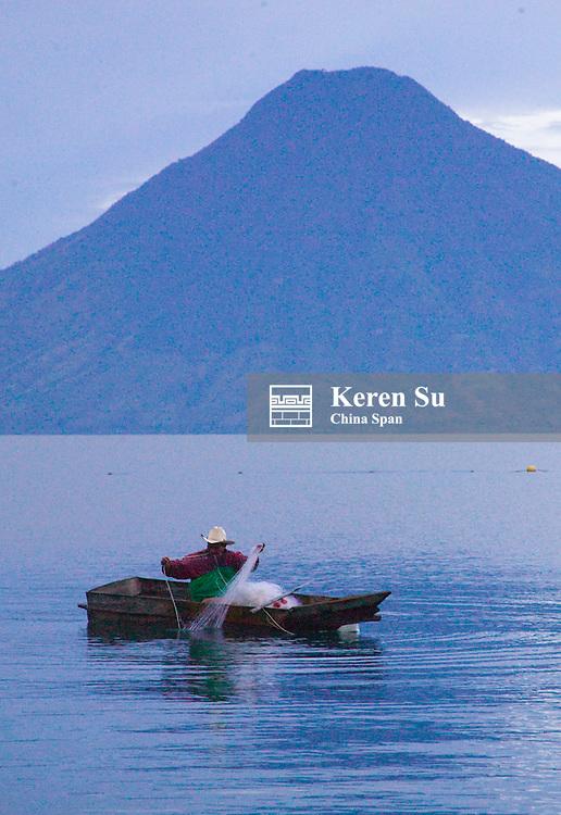 Fisherman on canoe on Lake Atitlan, Volcano San Pedro in the distance, Santiago, Guatemala