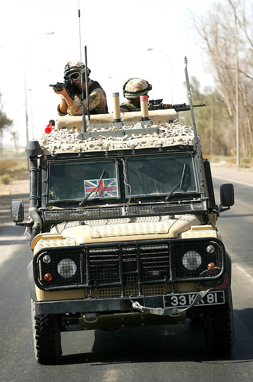 Baghdad, Iraq, 2 Oct 2005. Running 'Route Irish'...Armoured Land Rovers used by British Forces.....B Company, 1st Battalion, The Royal Irish Regiment, a tight-knit multi national fighting force make daily escorting runs along ?Route Irish?, the infamous Baghdad Airport road. The 46 man team are all British Army regulars but come from as far afield as Fiji, South Africa and Northern and Southern Ireland. Previous deployments in Kosovo, Sierra Leone and Northern Ireland have equipped them with the valuable skills needed to provide protection for British Forces and materials transiting the world?s most dangerous highway. Due to an increased presence of US forces along the route both in dug in positions and mobile patrols, attacks along the road have slackened, despite this a day rarely passed without an IED (improvised explosive device) being detonated or a small arms attack against coalition forces. ..The convoy attempts to maintain a seclusion ?bubble? around its vehicles for the duration of the journey. Any civilian vehicle that either strays into the bubble or refuses to keep their distance represents a threat and should they ignore the warning blasts on air horns carried in each vehicle the rules of engagement progress from warning shots to use of lethal force. The relative safety of the International Zone offers them an opportunity to decompress between missions. A duty driver ferries soldiers to the ?Liberty Pool?. Once only frequented by Iraq?s Ba?athist elite the luxury swimming pool and gym now fills with troops. Their body armour, helmets and weapons all within easy reach they either soak up the sun or compete with each other in diving competitions. After a daily briefing the troops have access to the ?Mosquito and Camel? bar where they watch TV or play pool and in accordance with the ?2 can rule? are allowed to drink 2 beers per night.