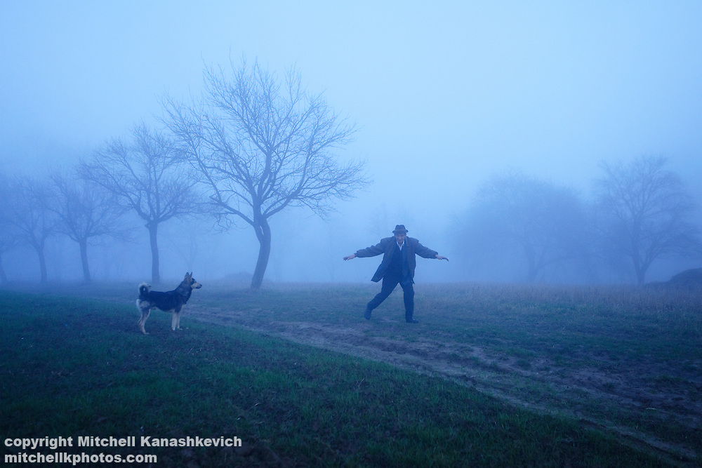 A rural Romanian man plays with his dog on a foggy day in the region of Maramures
