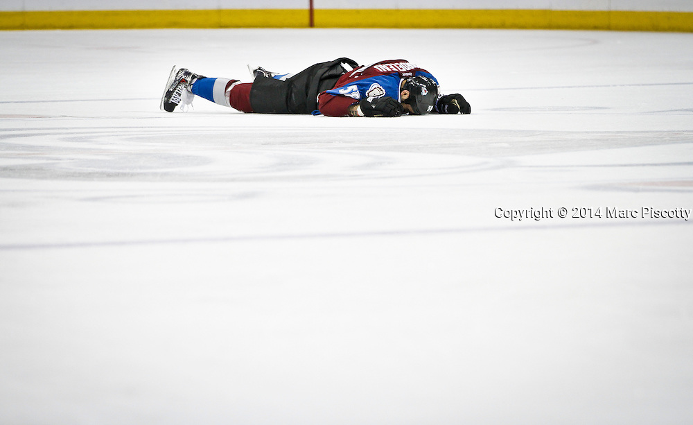 SHOT 3/8/14 4:14:43 PM - The Colorado Avalanche's Patrick Bordeleau #58 lays on the ice face down after a hit while playing against the St. Louis Blues during their regular season Western Conference game at the Pepsi Center in Denver, Co. The Blues won the game 2-1.<br /> (Photo by Marc Piscotty / &copy; 2014)
