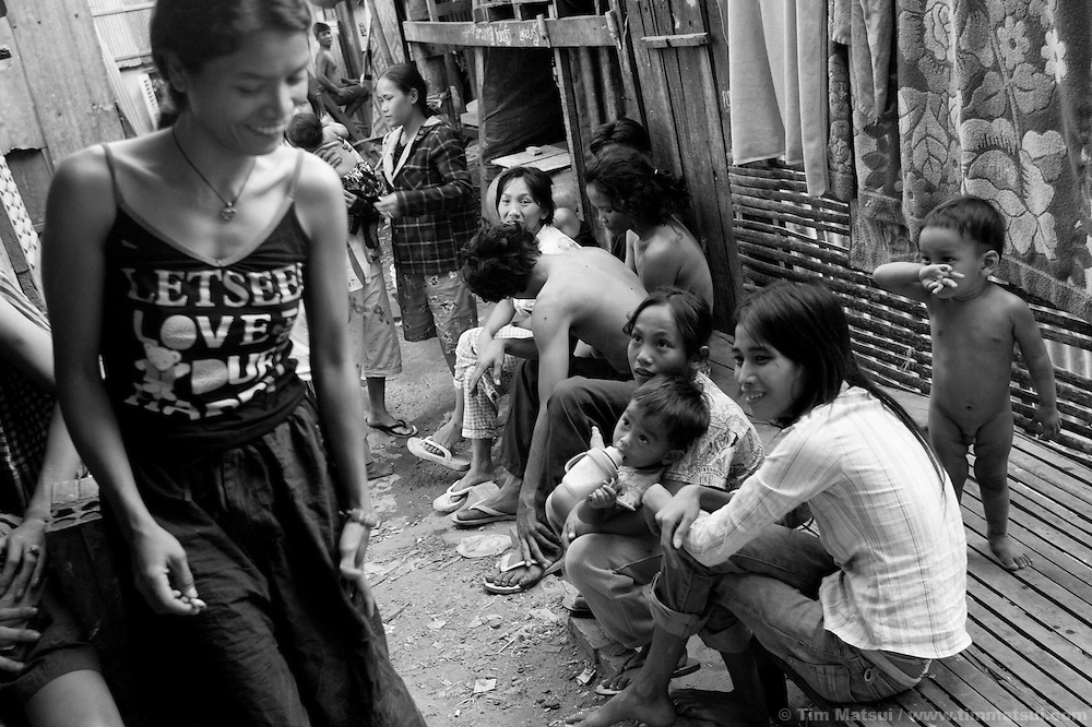 """Prostitute Srey Bee (left) relaxes before a night of work while at home in the slum where the non governmental organization """"Acting for Women in Distressing Situations"""" (AFESIP), conducts outreach and provides services in Phnom Penh, Cambodia. The permanent structure, a decaying four story building known simply as 'The Building', was built in the 1960's as transitional housing and now hosts a shantytown where many of the city's poor live, including many prostitutes, and is believed to have the highest rate of HIV infection in the city. AFESIP hands out free condoms, instructs prostitutes on HIV prevention, and conducts outreach in case the prostitutes need medical services, choose to leave their profession, or can report on cases of sex trafficking. AFESIP offers housing, education, training, and counseling for women who are victims of sex trafficking, worked as prostitutes, or are escaping domestic violence. Founded by Somaly Mam, who herself was once a prostitute and victim of trafficking and domestic abuse, AFESIP has three facilities in Cambodia and works with other NGO's to provide long term care for the women."""