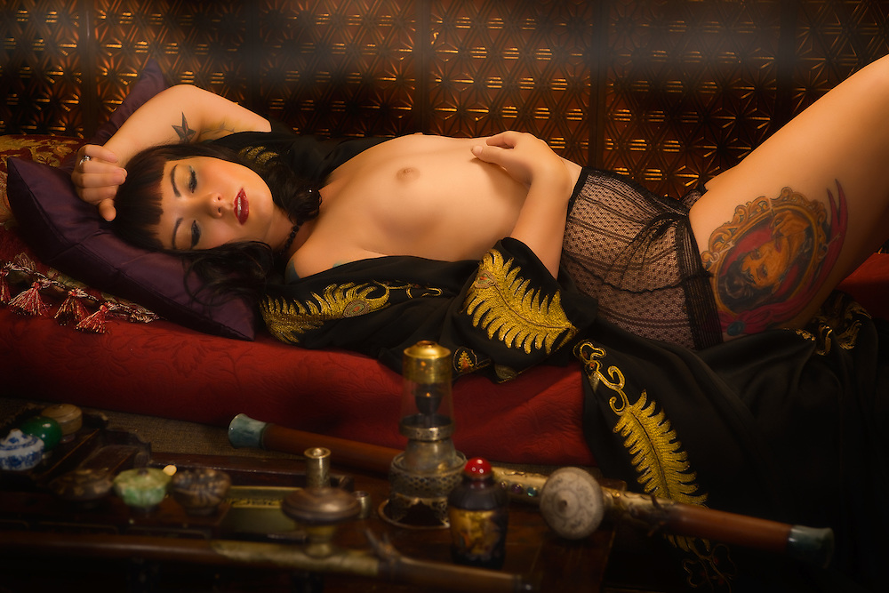 """Am I not desirable? Seductive, beautiful woman in a very erotic pose,  portrayed by alternative model Sabrina Sin, smoking opium in an ornate pipe, a forbidden pleasure among the liberated French females of the 1930's. She is being carried away by the effects of the drug surrendering herself to the drug. This collection was inspired by the writings of Brassai in his book """"The Secret Paris of the 1930's""""."""