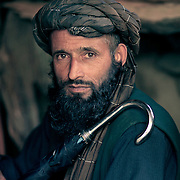 A Gujjar man sits proudly with his umbrella. This image shows the classic Gujjar turban.