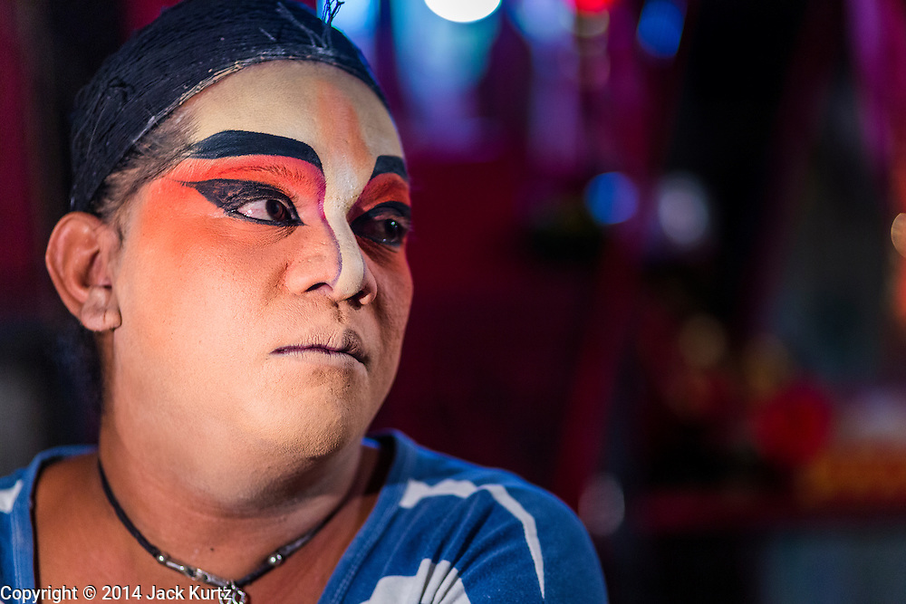 """25 JANUARY 2014 - BANG LUANG, NAKHON PATHOM, THAILAND: A performer with the Sing Tong Teochew opera troupe before a show in a Chinese shrine in the town of Bang Luang, Nakhon Pathom, Thailand. The Sing Tong Teochew opera troupe has been together for 60 years and travels through central Thailand and Bangkok performing for mostly ethnic Chinese audiences. Chinese opera was once very popular in Thailand, where it is called """"Ngiew."""" It is usually performed in the Teochew language. Millions of Chinese emigrated to Thailand (then Siam) in the 18th and 19th centuries and brought their cultural practices with them. Recently the popularity of ngiew has faded as people turn to performances of opera on DVD or movies. There are still as many 30 Chinese opera troupes left in Bangkok and its environs. They are especially busy during Chinese New Year when travel from Chinese temple to Chinese temple performing on stages they put up in streets near the temple, sometimes sleeping on hammocks they sling under their stage.     PHOTO BY JACK KURTZ"""